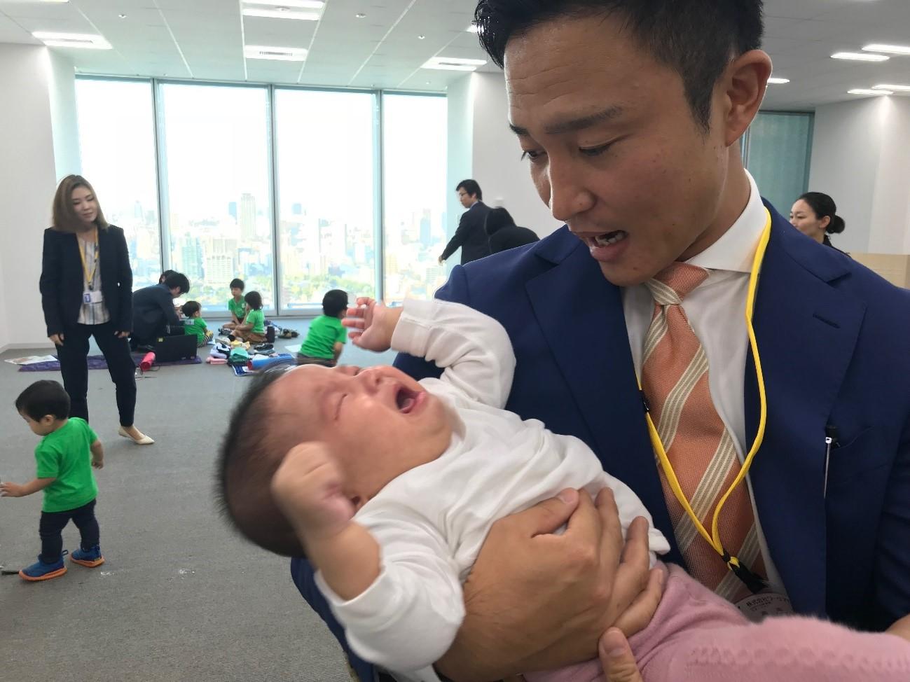 赤ちゃんを抱くスーツの男性